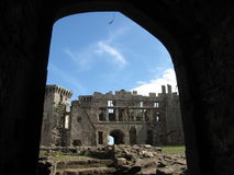 Raglan Castle. Ruin in Wales on a clear and cloudy day, taken through a doorway with a view of the walls, façade, other doorways, a tower, steps and the window Royalty Free Stock Images