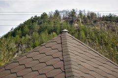 Ragment des Dachs bedeckt mit flexiblen Schindeln in Form von Bienenwabe auf dem Hintergrund des Berges lizenzfreie stockbilder
