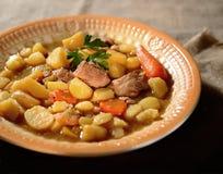 Ragoût de boeuf frais, pommes de terre, verts, épices originales dans le plat en céramique image stock