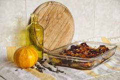 Ragout, cutting board, bottle and a pumpkin on a towel. Ragout, made of vegetables, cutting board, a bottle and yellow pumpkin on a striped towel stock photo