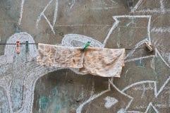Rags che appende su una linea di vecchia parete fotografia stock libera da diritti