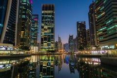 Ragt im Stadtzentrum gelegene Nachtszene Dubais, Jumeirah See hoch Lizenzfreie Stockfotografie
