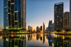 Ragt im Stadtzentrum gelegene Nachtszene Dubais, Jumeirah See hoch Lizenzfreies Stockfoto
