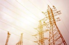 Ragt Stromleitungen gegen einen Hintergrund des bewölkten Himmels hoch elektrizität stockbild