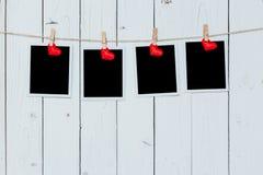 Rahmen mit vier Fotos leer und rotes Herz, das am weißen hölzernen backg hängt Lizenzfreie Stockfotografie