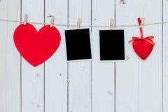 Rahmen mit zwei Fotos leer und rotes Herz, das am weißen hölzernen backgr hängt Lizenzfreie Stockfotografie