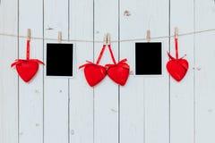 Rahmen mit zwei Fotos leer und rotes Herz, das am weißen hölzernen backgr hängt Stockfotografie