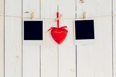 Rahmen mit zwei Fotos leer und rotes Herz, das am weißen Holz mit s hängt Stockfotografie