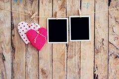 Rahmen mit zwei Herzen und mit zwei Fotos, der am Wäscheleineseil mit w hängt Stockfoto