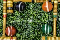 Rahmen von Krocketschlägern und Bällen auf Gras Stockfotos