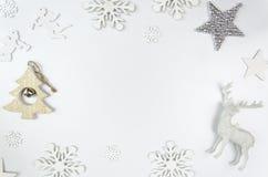 Rahmenmodell der frohen Weihnachten Weihnachtsrotwild, Silberstern und Schneeflocken Sauberes Modell Flatlay Stockfoto