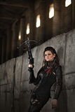 Raider girl in leather costume with a crossbow at post-apocalyptic world. Stock Photos