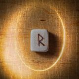 Raidho. Handmade scandinavian wooden runes on a wooden vintage background in a circle of light. Concept of fortune stock photo