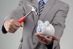 Raiding the piggy bank. Businessman with hammer about to smash piggy bank to get at corporate savings Stock Images