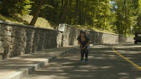 Raies de rouleau heureux d'équitation de femme à la vitesse en descendant banque de vidéos