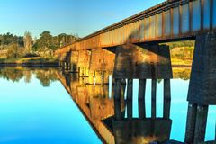 A rail bridge crosses a slow-moving river. A rural landscape with a rusty old concrete and metal rail bridge, reflected in the glassy water of a quiet river stock photo