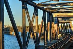 Rail bron över vatten som fångar de sista strålarna av solen arkivfoton