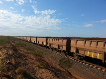 Rail carriages filled with Iron ore Western Australia. Pilbara Western Australia Iron ore filled railway carriages on a train line into the horizon from a mine Stock Photos