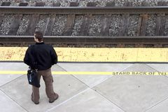 Rail Commuter. A man awaits the train for his morning commute to work royalty free stock photo