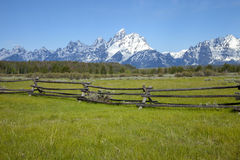 Rail fence in field below Grand Tetons mountains. Rail fence in field with the Grand Tetons range behind Stock Photo