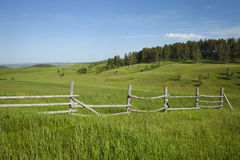 Rail fence and hills with pines in Montana Royalty Free Stock Photo