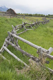 A rail fence leads into an old historic barn. royalty free stock images