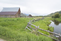 A rail fence leads into an old historic barn. Royalty Free Stock Photography