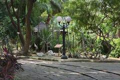 Rail ferroviaire à un parc, à une route en pierre, à un réverbère et à une forêt images stock