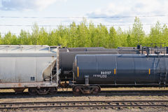 Rail freight cars. Closeup of freight cars and tankers on railway, forest in background Royalty Free Stock Images