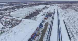 Rail Freight Marshalling Yard. Aerial view of freight trains with cargo containers on a sunny winter day. Flying over railway yard with a lot of railway lines stock footage