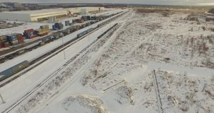 Rail Freight Marshalling Yard. Aerial view of freight trains with cargo containers on a sunny winter day. Flying over railway yard with a lot of railway lines stock video footage