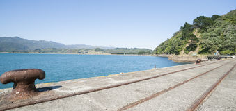 Rail lines and bollard on disused wharf. Royalty Free Stock Image