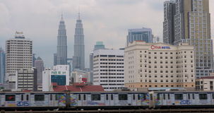 By rail passes train. In the background seen Petronas Twin Towers, hotel and skyscrapers stock video