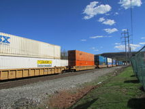 Rail road cars with intermodal containers of CSX, JB Hunt, Swift and Schneider passing by West Haverstraw, NY. Stock Image
