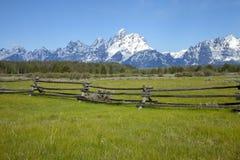 Rail staket i fält nedanför tusen dollarTetons berg Arkivfoto