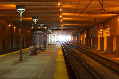 Rail Station. A rail station platform with orange or dim lights. Perspective view with a vanishing point at the end of the tunnel Stock Images