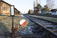 Rail switch. Old rusty railway switch with red and white colors next to rails at sunset stock photo