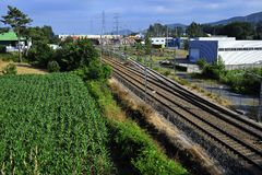 Rail track on the countryside. Rail track crossing agricultural fields and industrial state on north Portugal Porto region royalty free stock photo