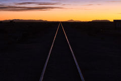 Rail track through the desert at sunset Royalty Free Stock Images