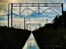 Rail track reflecting blue sky and railroad infrastructure. Polished shining rail and railroad infrastructure. High contrast photo. Old railroad between Góra stock images
