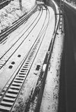 Rail track side by side with road black and white during winter inside city center no people no cars. Shot from up high inside city limits Stock Photo