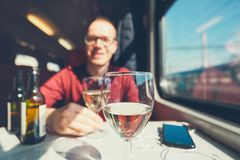 Young man traveling by train. Rail transportation in sunny day. Smiling young man drinking wine wine on passenger train. Selective focus on the wineglass Royalty Free Stock Photos