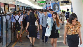 Rail Travellers Pass Through A Train Station. Rail travellers pass through a BTS Skytrain station during rush hour on June 4, 2014 in Bangkok, Thailand. Launched Stock Images