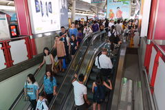 Rail Travellers Pass Through A Train Station. Rail travellers pass through a BTS Skytrain station during rush hour on June 4, 2014 in Bangkok, Thailand. Launched Stock Photos