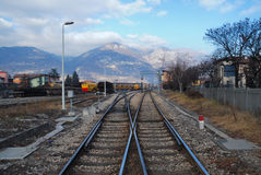 Rail Yard near Brescia, Italy. A view of intersecting railroad tracks and a rail yard near Brescia, Italy with pretty mountains in the distance stock images