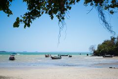 Railay, Thailand - May 12, 2019: Low tide on the eastern part of the beach. Traditional Thai long-tailed boats are almost on sand. Coast landscape ocean sea stock image