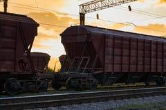 Railcar voor droge lading tijdens mooie zonsondergang en kleurrijke hemel, spoorweginfrastructuur, vervoer en industrieel concept stock fotografie