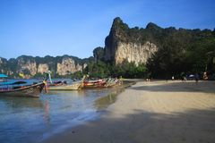 RAILEY KRABI, THAILAND - JANUARY 3. 2017: View on secluded beach with high steep limestone cliffs and traditional thai long-tail stock images