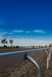 Railing Around Horse Race Track. A metal railing surrounds the dirt race track of a popular venue stock image