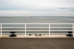 Railing of pier with ocean view in cloudy calm day with ships on horizon stock photo